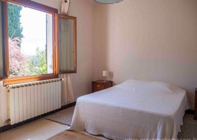 Chambre avec grand lit, chevets et lampes, fenêtre, tapis de sol