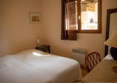 Chambre avec 2 lits simples réunis pour former un lit double, chevets, lampes, cadres décoratifs, fenêtre et rideaux, bureau