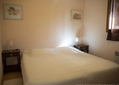 Chambre avec 2 lits simples réunis pour former un lit double, chevets, lampes, cadres décoratifs, fenêtre et rideaux