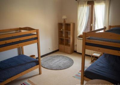 Chambre dortoir, avec 4 lits superposés, tapis de sol, meuble rangement, lampes de chevet, fenêtre sud