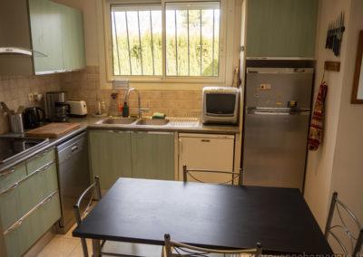 Cuisine équipée, table et chaises, plaques 4 feux, évier 2 bacs, lave-vaisselle,four microondes, réfrigérateur congélateur, fenêtre donnant sur verdure