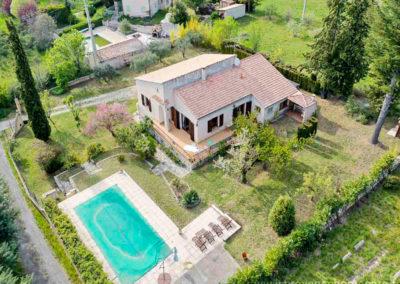 vue aerienne de la propriété, avec le grand terrain arboré, piscine, maison, transats et parasol