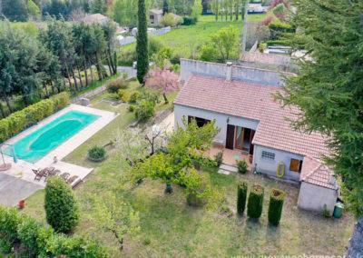 vue aerienne de la propriété avec le grand terrain arboré, la piscine, la maison