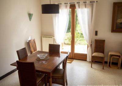 Salle à manger, table avec rallonge, chaises en bois, tableau, porte fenêtre donnant sur terrasse