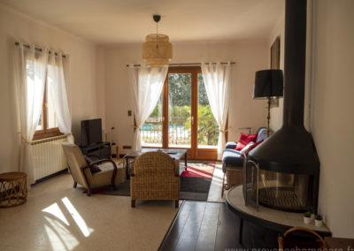 Salon, avec 2 fauteuils, canapé 3 places, cheminée, télévision écran plat, tapis, meubles divers, baie vitrée donnant sur la terrasse et la piscine