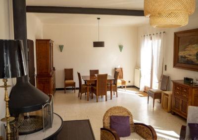 Salle à manger, grand salon, table et chaises, fauteuils et canapé, porte vitrée, soleil