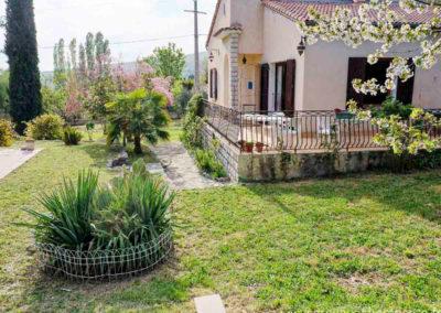 Pelouse, terrasse devant la maison, table et chaises, cactus et arbustes fleuris