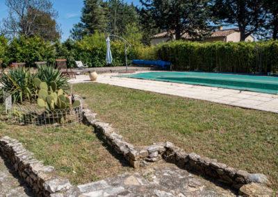 Cactus, herbe, verte devant la piscine, parasol, transats, dallage de pierres