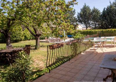 Terrasse, table et chaises de jardin, arbres, vue sur la piscine