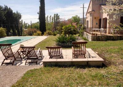 Transats devant la piscine, la maison avec la terrasse, arbustes et terrain arboré