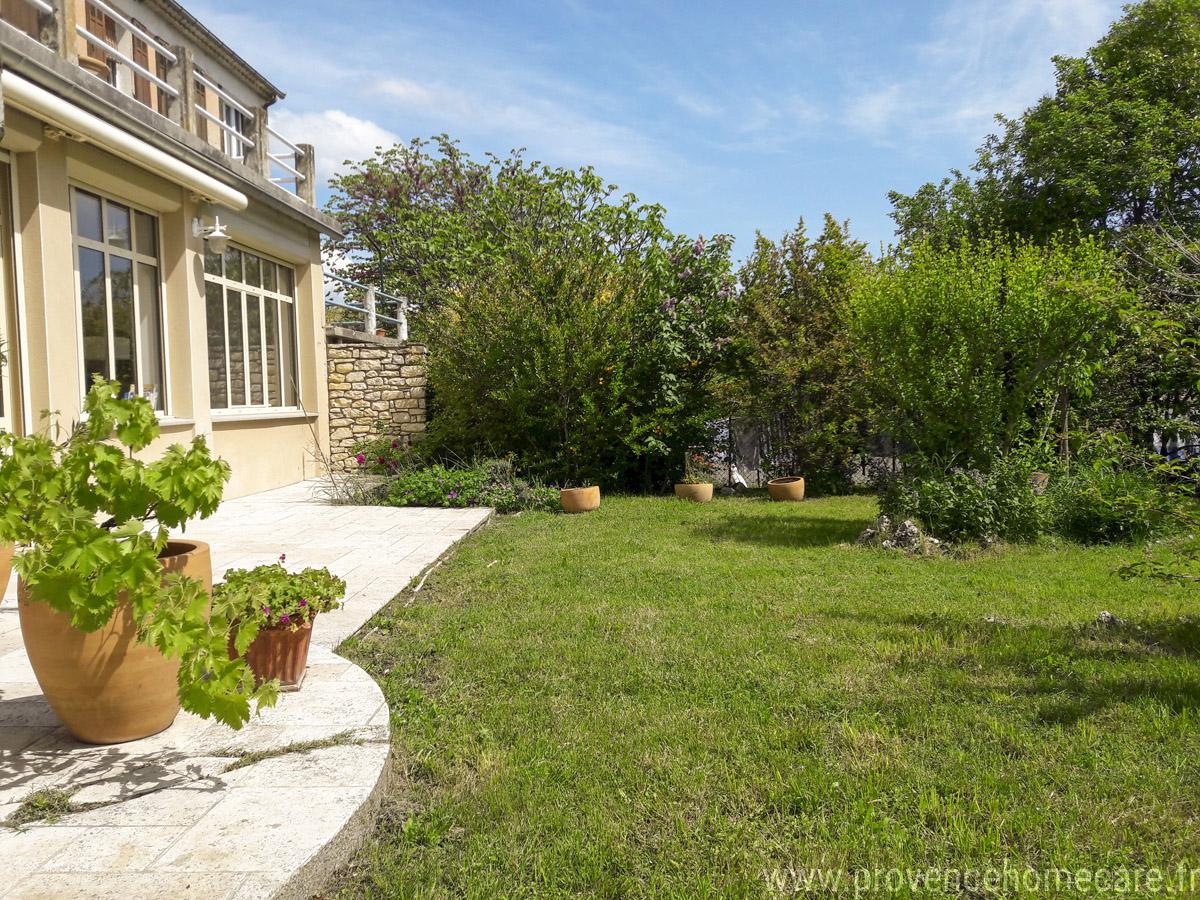 grand salon avec canapé d'angle et fauteilles trés ensoleillé avec acces au jardin