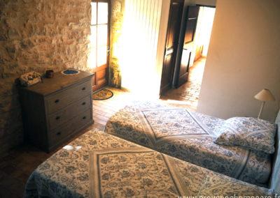 Chambre avec deux lits simples en ré de villa, commode rustique, tomettes Provençales, WC et salle de bain, maison gérée par l'agence Provence Home care
