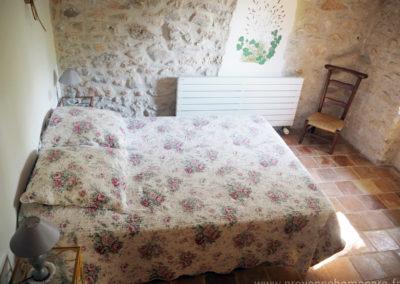Chambre avec grand lit double, chevets, murs en pierres, à l'etage, maison gérée par l'agence Provence Home care
