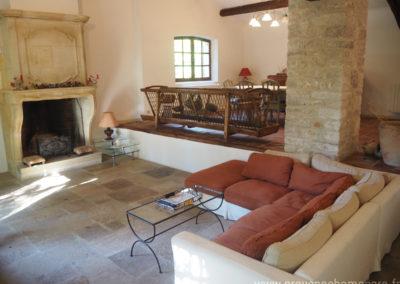 Salon avec canapé d'angle, table basse, sol dallé, cheminée ancienn, devant la salle à manger, fenêtre laissant passer le soleil, table et chaises, maison gérée par l'agence Provence Home care