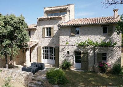 Vue aérienne sur terrasse avec salon de jardin, jardinet devant portes vitrées de la maison en pierres, solarium, ciel bleu, maison gérée par l'agence Provence Home care