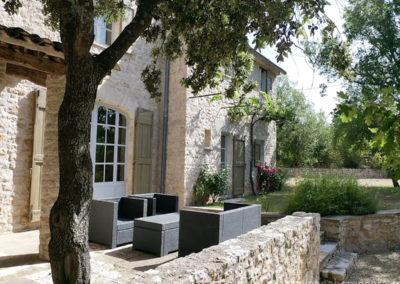 Salon de jardin sur la terrasse en pierres à l'ombre d'un chêne, jardin fleuri, villa gérée par l'agence Provence Home care