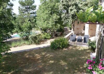 Vue sur jardinet et terrasse avec salon de jardin, nombreux arbres devant la piscine sécurisée, maison gérée par l'agence Provence Home care
