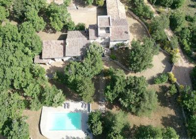 Vue aérienne sur la piscine, nombreux arbres, ancienne ferme en pierres au coeur du Luberon, maison gérée par l'agence Provence Home care