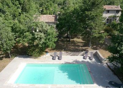 Vue aérienne de la piscine avec vue de la maison à travers les arbres, transats, terrain arboré et ombragé dans le Luberon, grande maison gérée par Provence Home Care