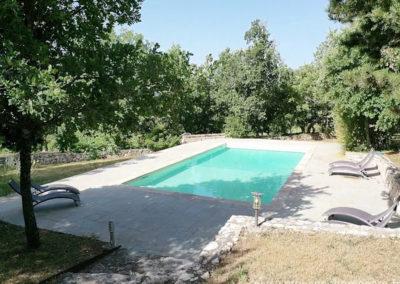 Piscine à l'eau claire avec transats sur grand terrain arboré et ombragé dans le Luberon, grande maison gérée par Provence Home Care