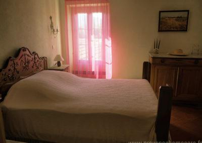 Chambre avec lit double à l'étage, tomettes Provençales, buffet rustique, fenêtre donnant sur la cour et le village médiéval de Dauphin dans le Luberon, maison gérée par l'agence provence Home care