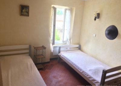 Chambre avec deux lits simples à l'étage, fenêtre ensoleillée donnant sur la cour et le village de Dauphin dans le Luberon, maison gérée par l'agence Provence Home care