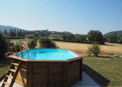 Vue piscine avec en fond le village médiéval de Dauphin dans le Luberon, maison gérée par l'agence Provence Home care