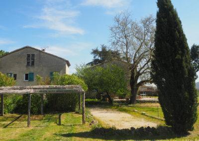 Vue sur le parking et le terrain de boules, arbres, maison gérée par l'agence Provence Home care